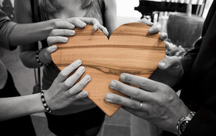 people holding a heart in healing circle